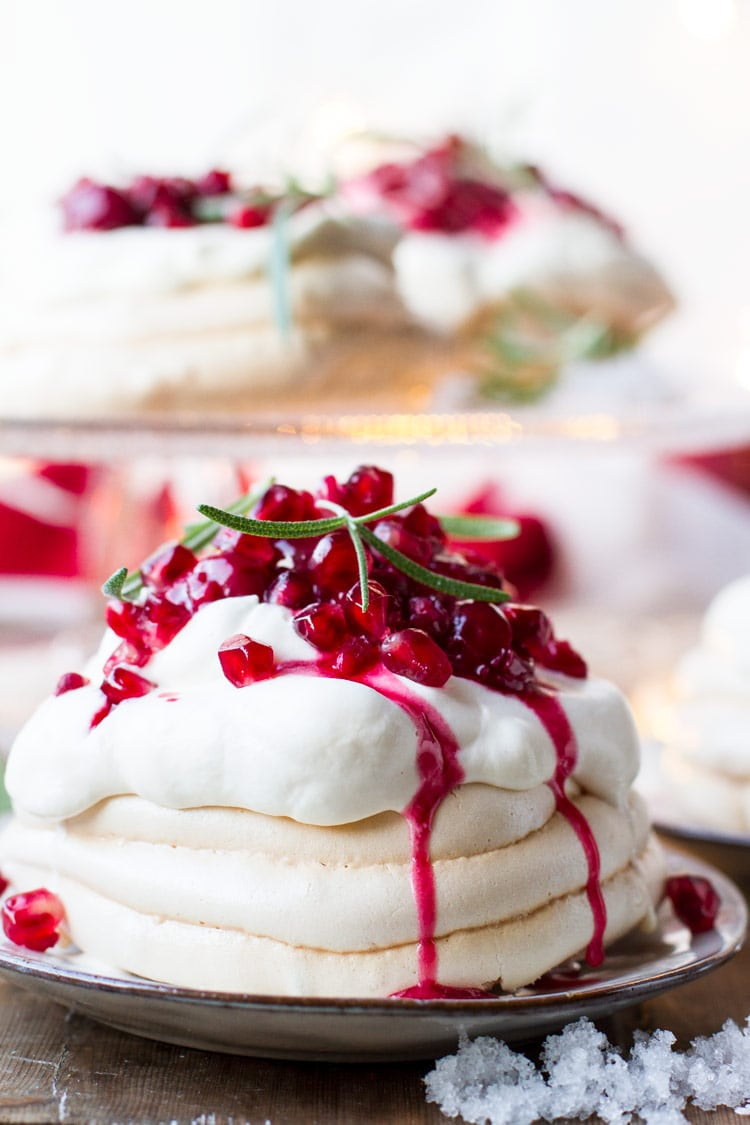Christmas Pavlova Dessert with whipped eggnog cream and cherry sauce dripping down the sides.