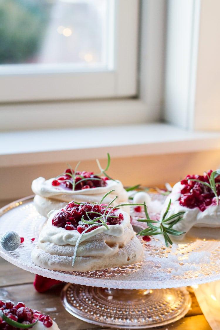 Three Christmas Pavlova Desserts with eggnog cream and cherry sauce, garnished with rosemary sprigs.