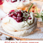 Christmas Pavlova Dessert with cherry sauce and rosemary sprig on a cake stand. Pinterest pin.
