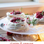 Three Christmas Pavlova Desserts with eggnog cream and cherry sauce, garnished with rosemary sprigs. Pinterest pin.
