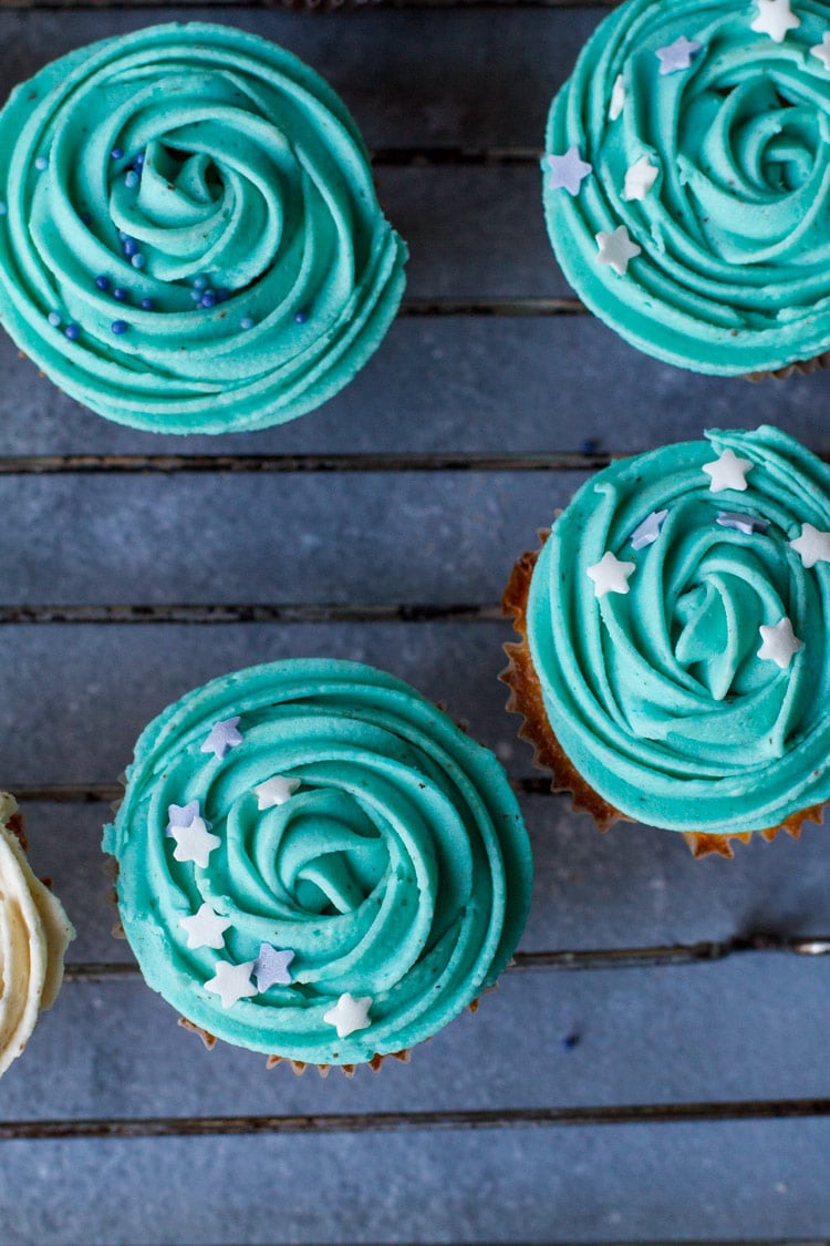 Cupcakes with turquoise buttercream frosting and star sprinkles. Flatlay.