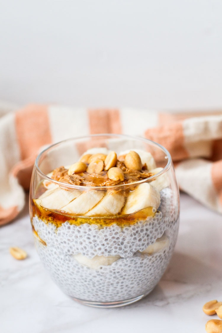 Round glass with chia pudding, topped with peanut butter, banana slices and maple syrup.