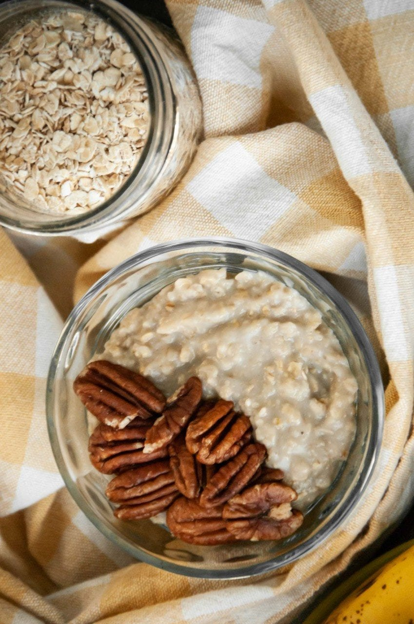 Oatmeal in a glass jar topped with pecan halves.