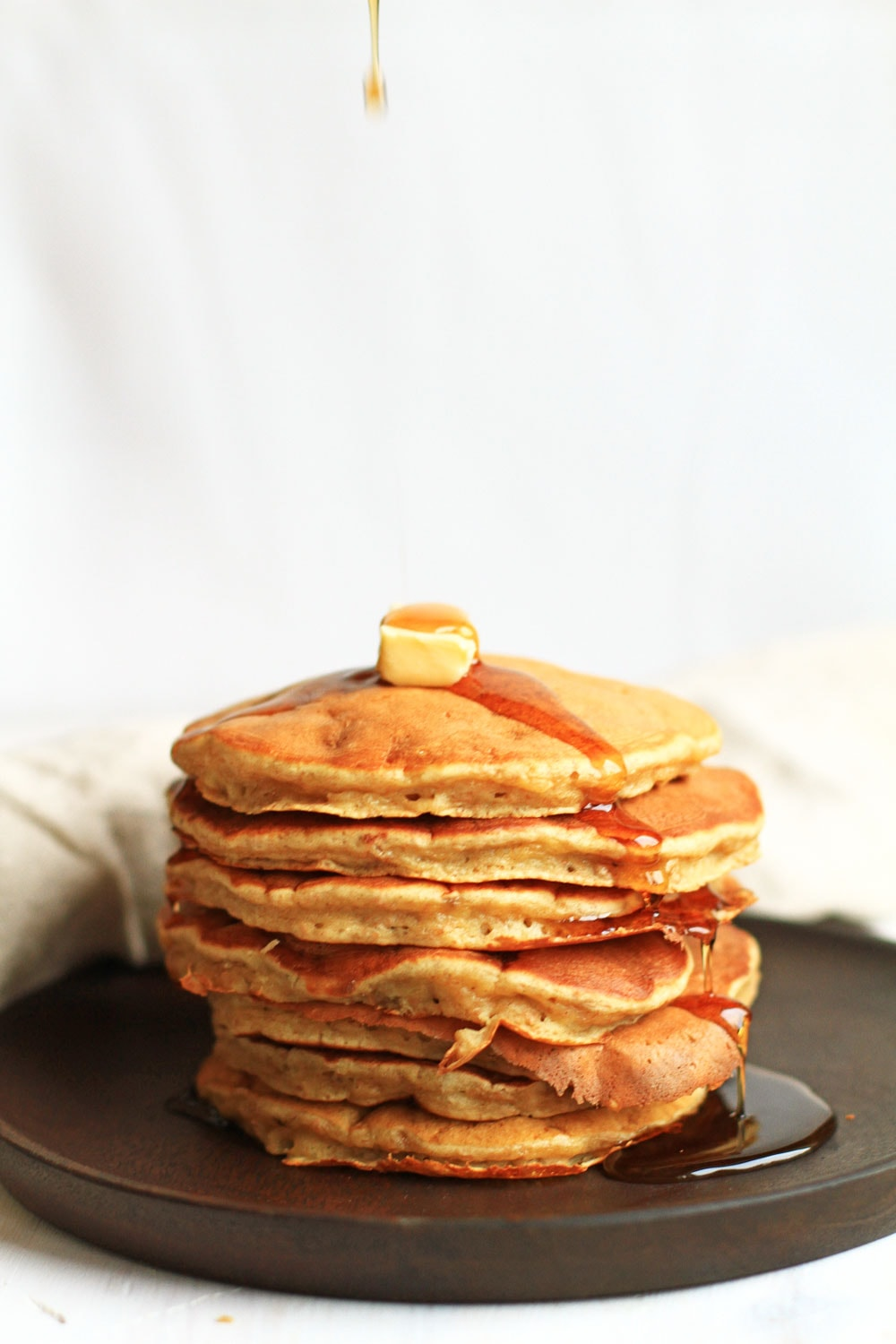 A stack of healthy banana pancakes. Topped with butter and maple syrup.