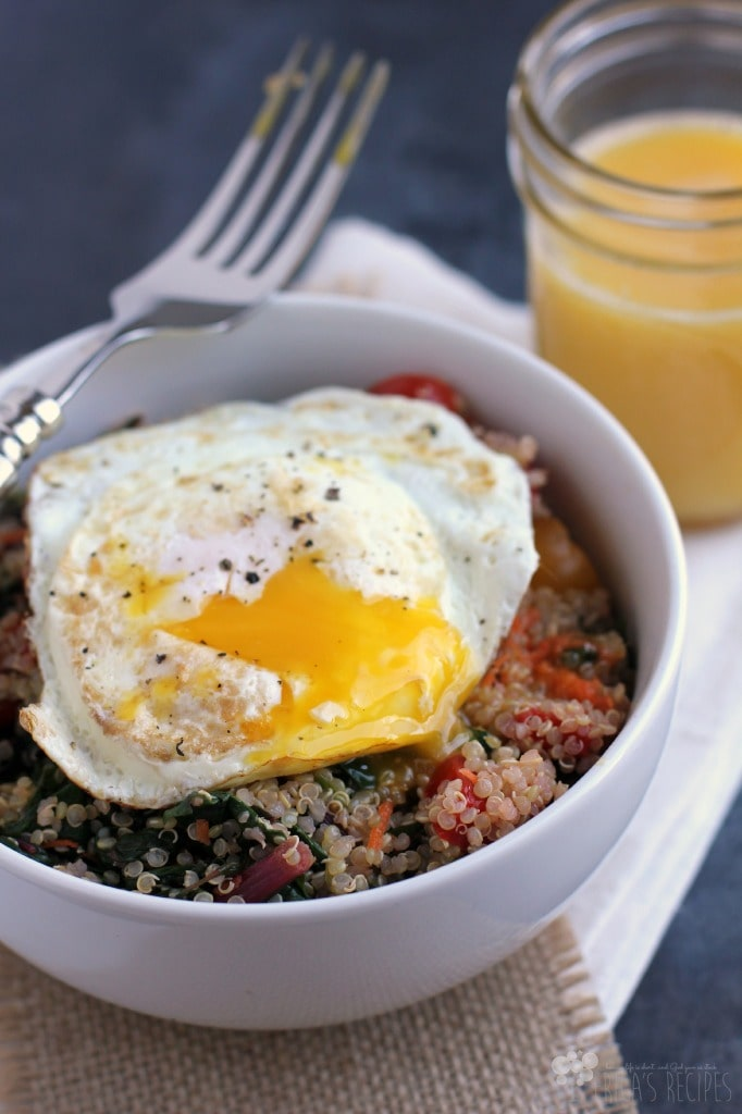 A white bowl with breakfast quinoa and sunny egg.