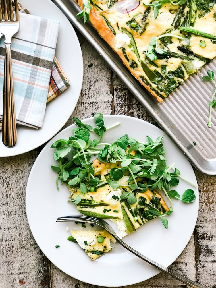 White plate with frittata and spring greens.