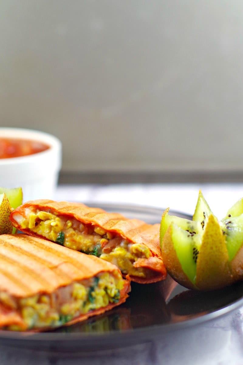 Healthy breakfast burrito cut in half, kiwi as decoration on the plate.