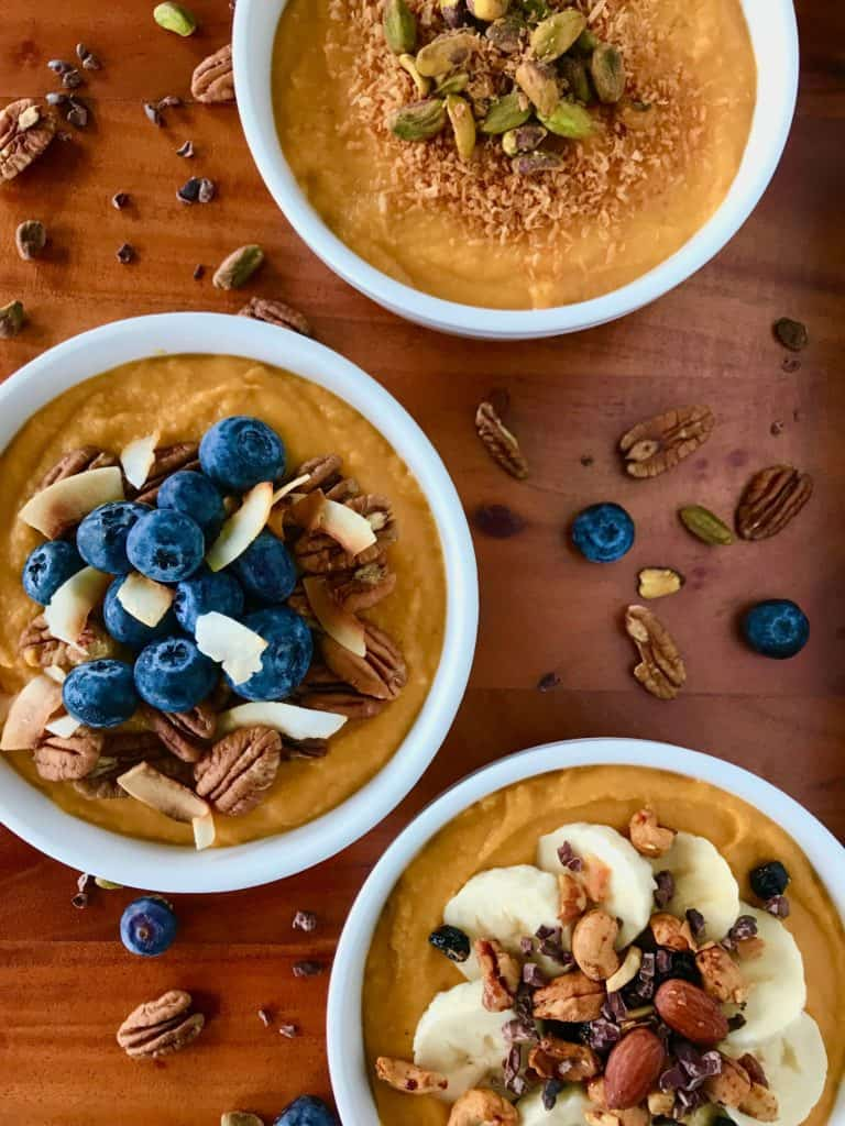 Three bowls of sweet potato smoothie, topped with pecans and blueberries.