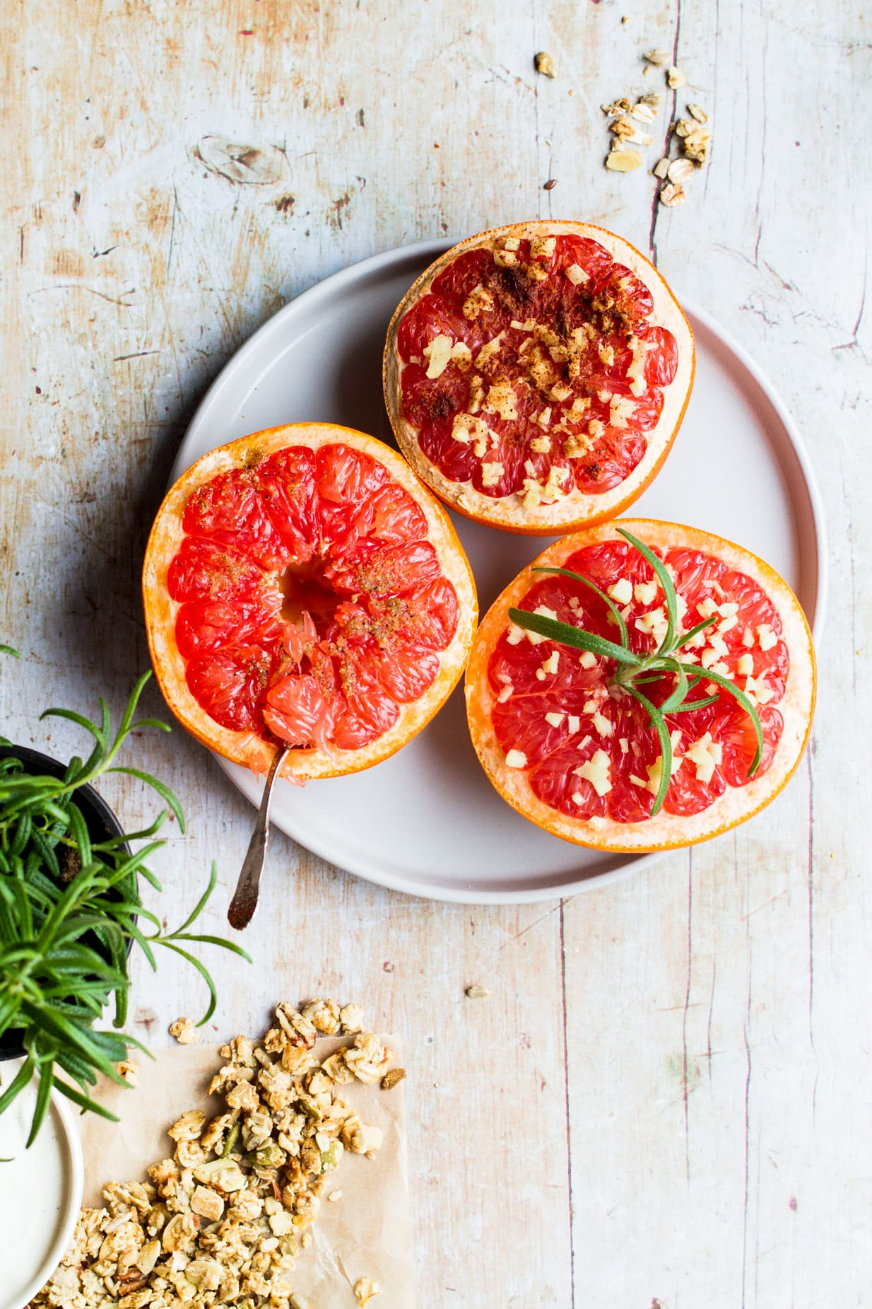 Three halves of baked grapefruit on a plate.