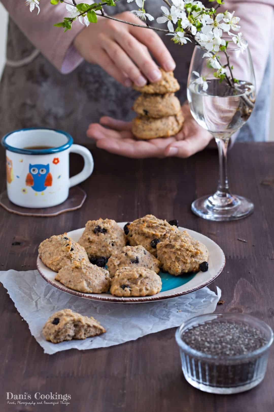 A plate with healthy breakfast cookies. Hands holding a stack in the background.