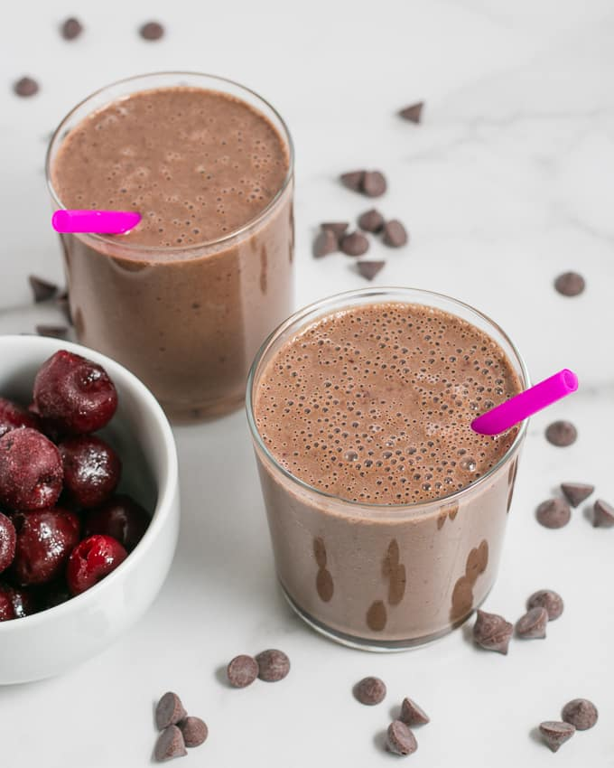 Two glasses with chocolate cherry breakfast smoothie, pink straws.