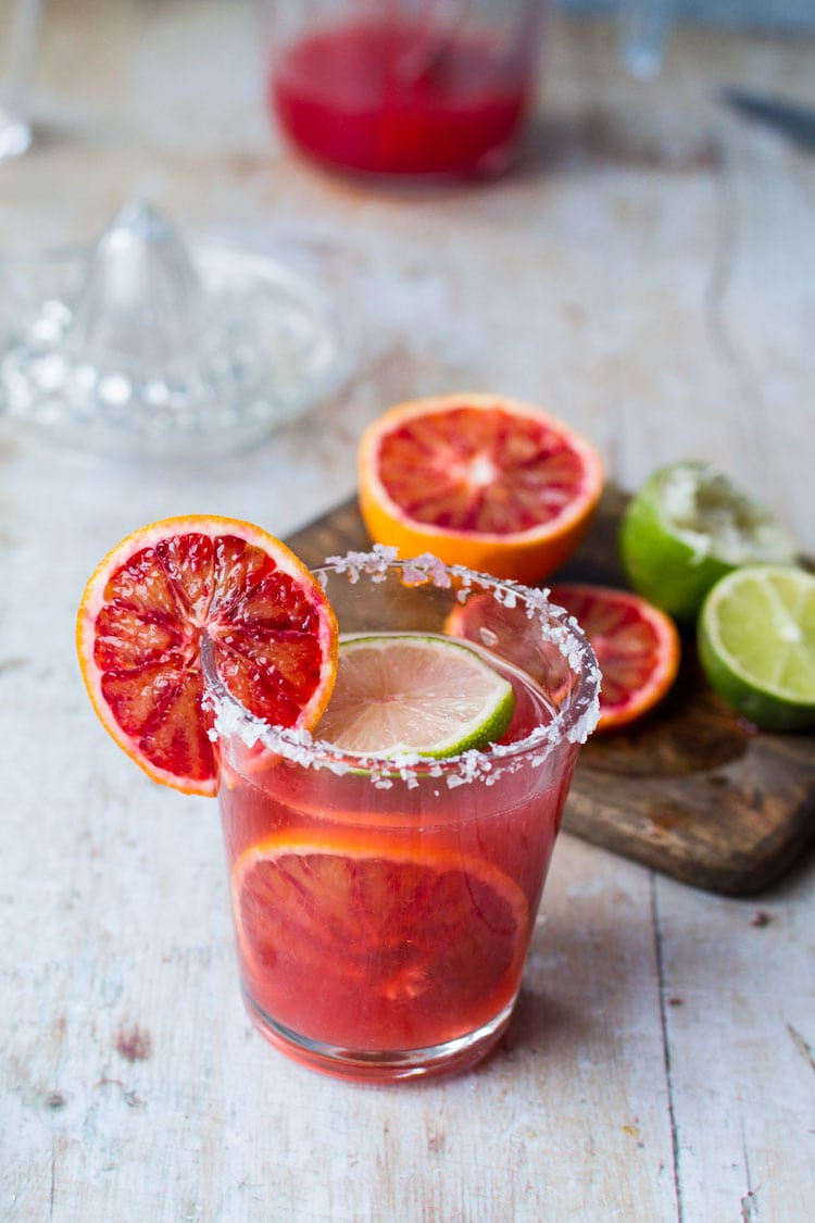 Glass with blood orange cocktail, slices of blood oranges and salted rim.