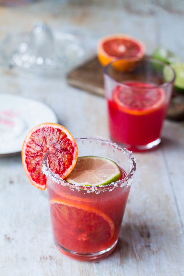 Two glasses with blood orange margarita. One has a blood orange garnish on the side.