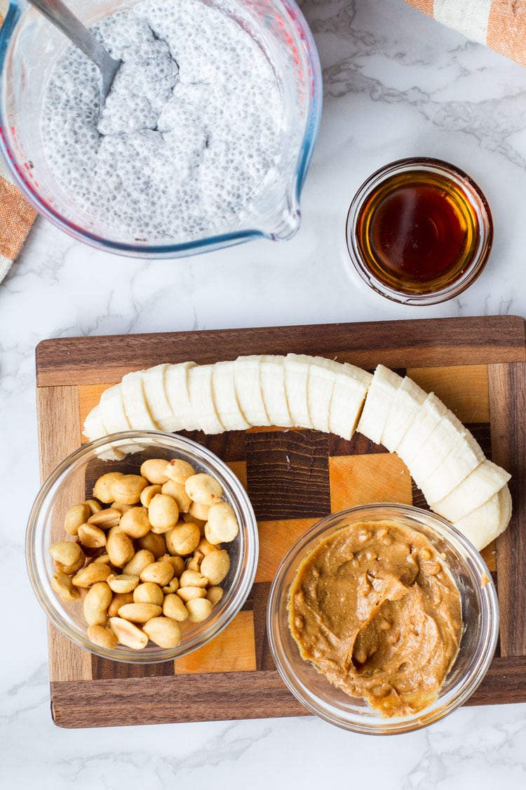 Wooden chopping board with slices bananas, bowls of peanuts and peanut butter.