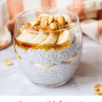Coconut chia pudding in a round glass with toppings such as banana and peanuts. Pinterest pin.