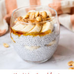 Round glass with chia pudding topped with sliced banana, peanut butter and peanuts. White background. Pinterest pin.