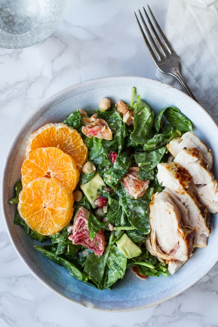 Winter salad with lemon chicken and clementine in a blue bowl.