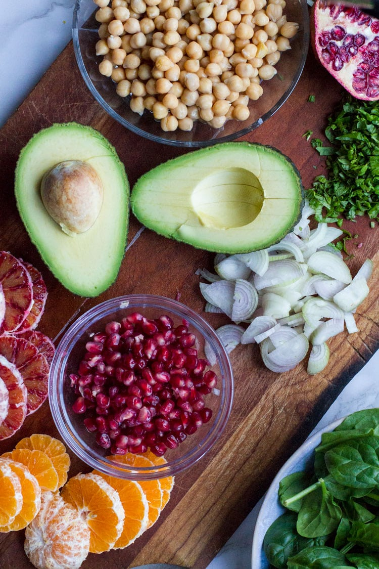 Salad ingredients on a cutting board; avocado, pomegranate, sliced onion, chickpeas etc.