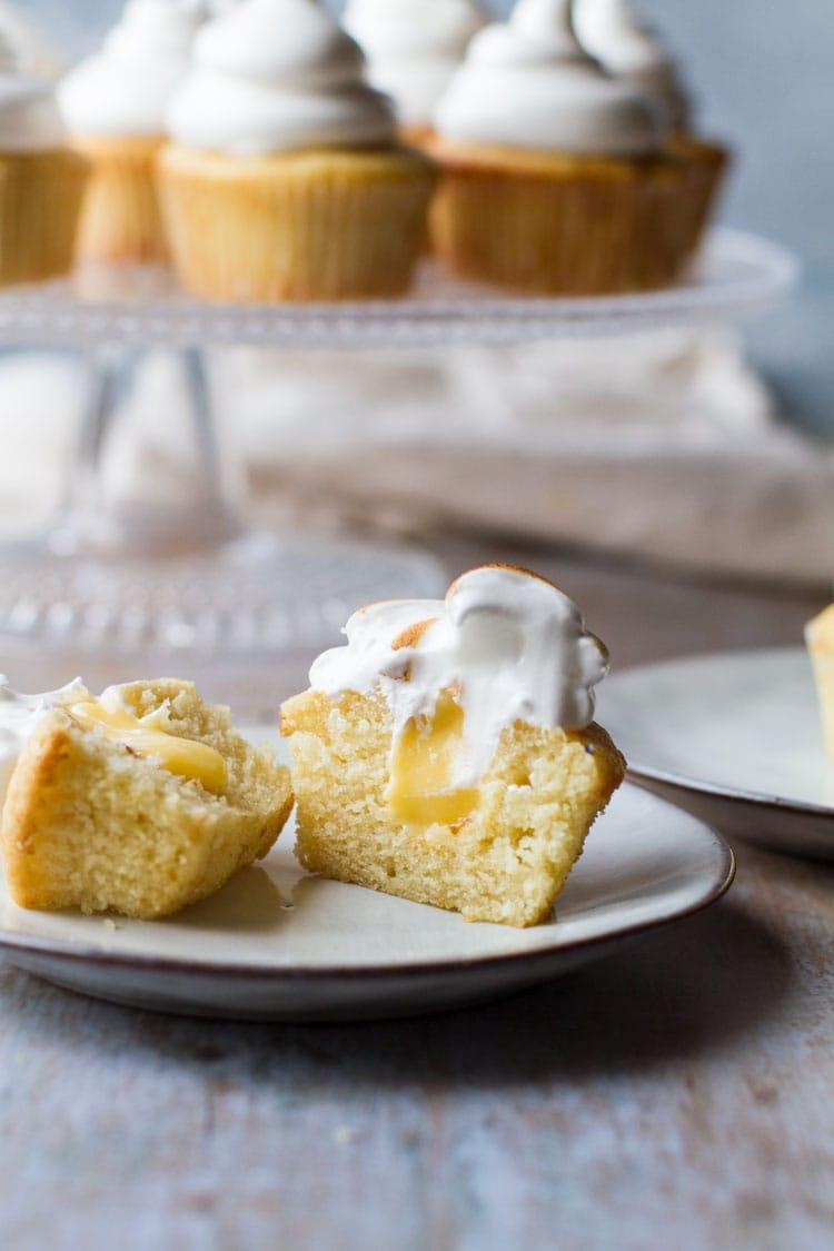 One lemon meringue cupcake cut open to show lemon curd oozing out.