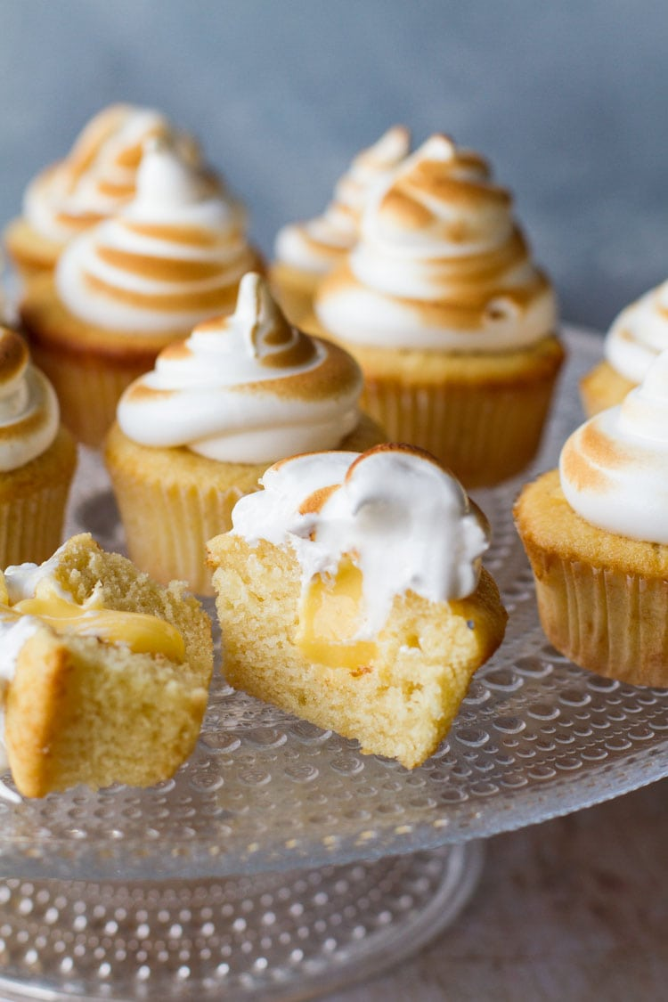 Cupcakes on a glass cake stand, with torched Swiss meringue. One cut open to show lemon curd.