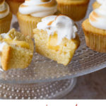 Cupcakes on a glass cake stand, with torched Swiss meringue. One cut open to show lemon curd. Pinterest pin with text at the bottom.