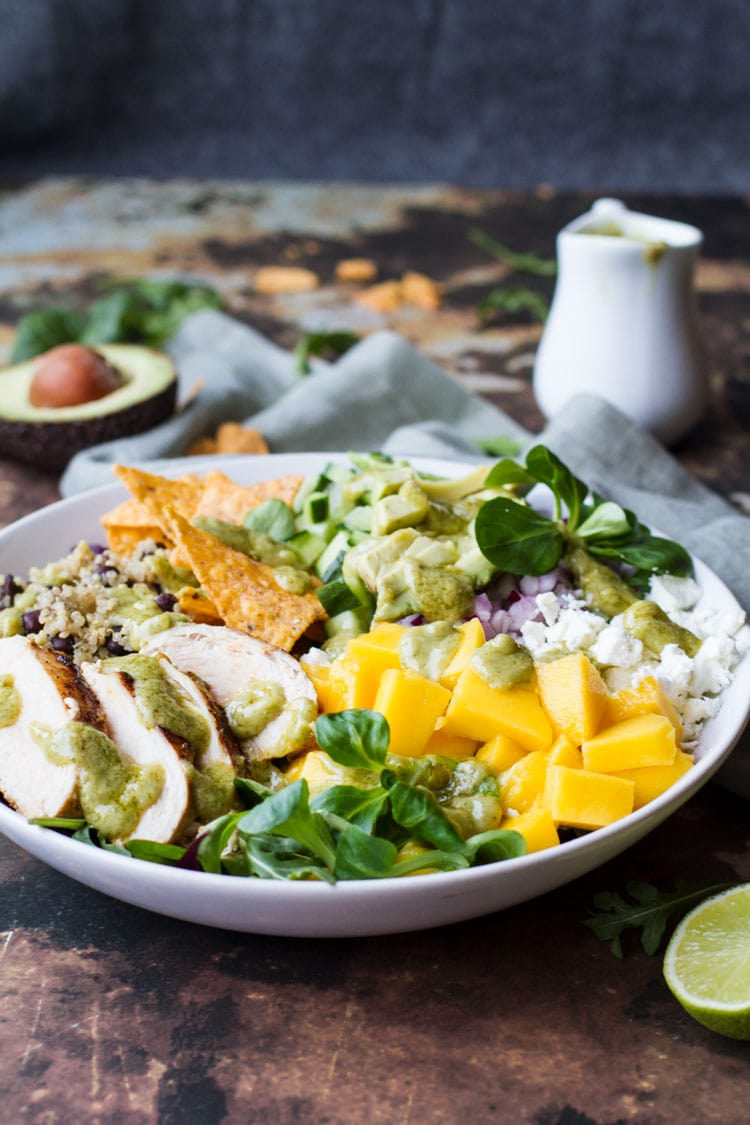 Big white bowl with ingredients like diced mango, sliced chicken, tortila chips and avocado slices.