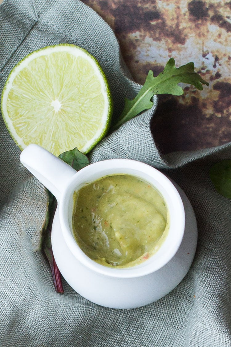 Avocado Herb Dressing in a small white jug. Half a lime on the side.
