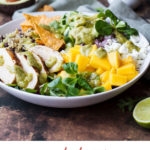 Big white bowl with ingredients like diced mango, sliced chicken, tortila chips and avocado slices. Pinterest pin.