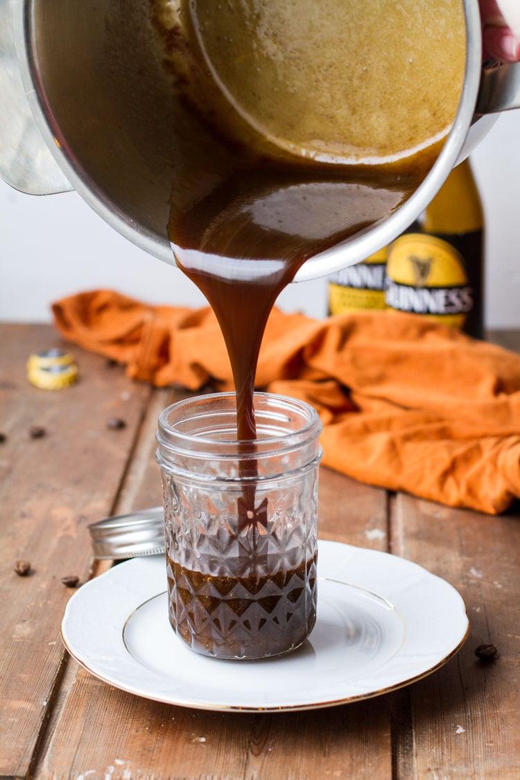 Pouring from a casserole, Guinness caramel sauce into a glass jar.