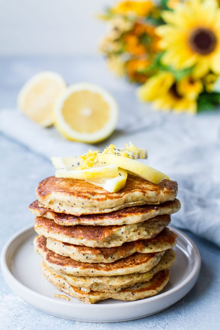 Stack of pancakes topped with lemon slices. Blue background.