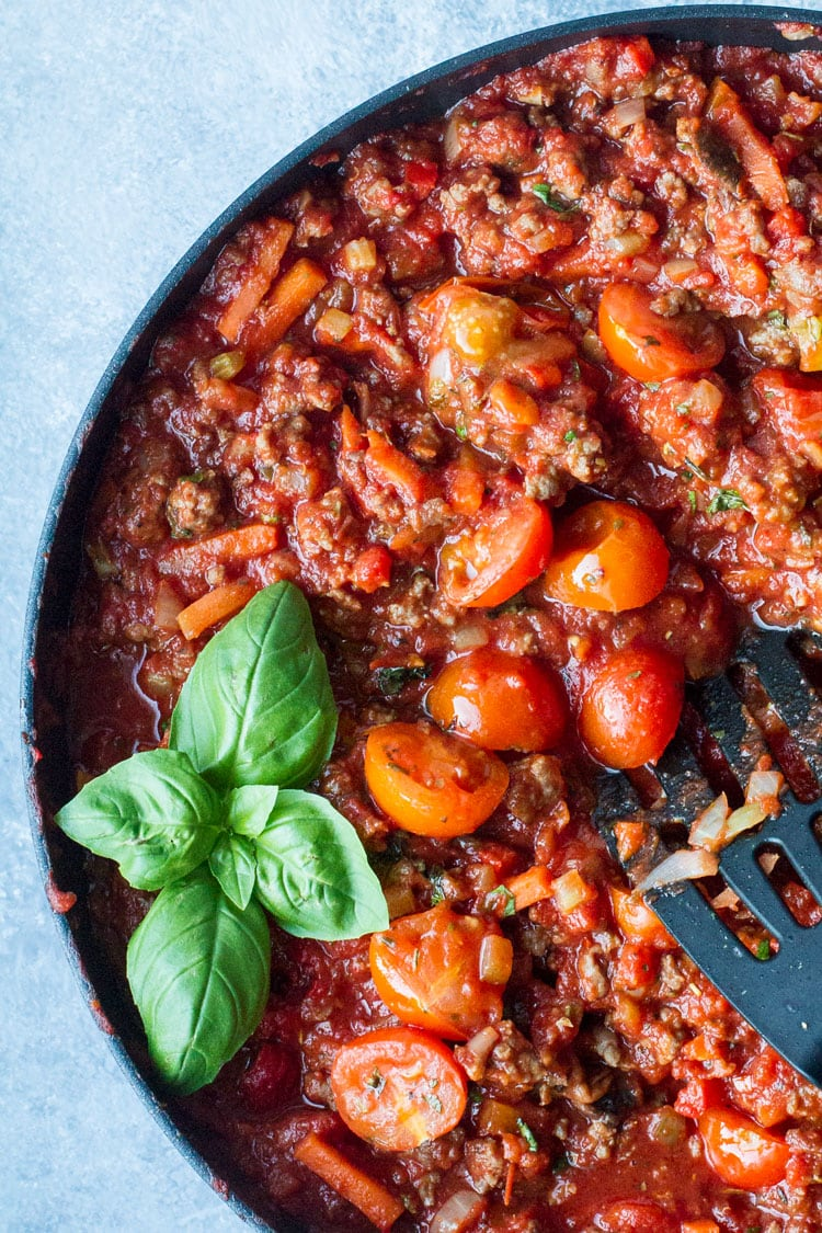 Bolognese sauce and cherry tomatoes in a large skillet, garnished with fresh basil.