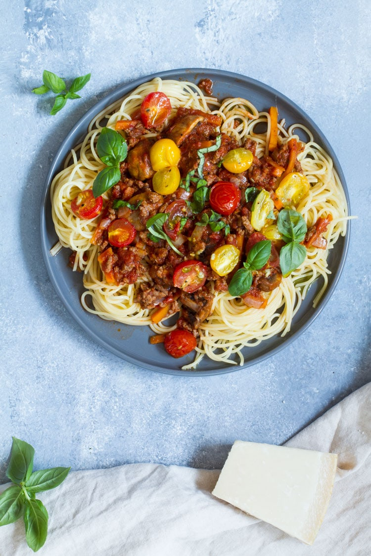 Plate with spaghetti and bolognese sauce with different colored cherry tomatoes.