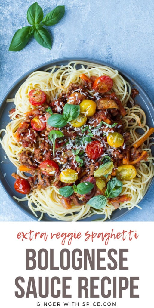 Spaghetti bolognese on a grey plate, blue background. Pinterest pin.