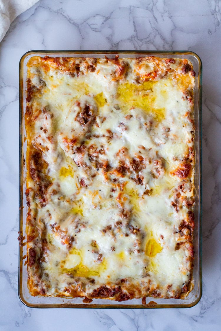 A whole casserole of homemade lasagna, topped with melted butter. Flatlay.