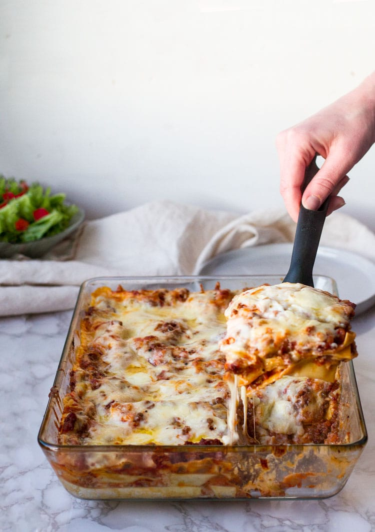Taking a slice of lasagna with a serving spoon.
