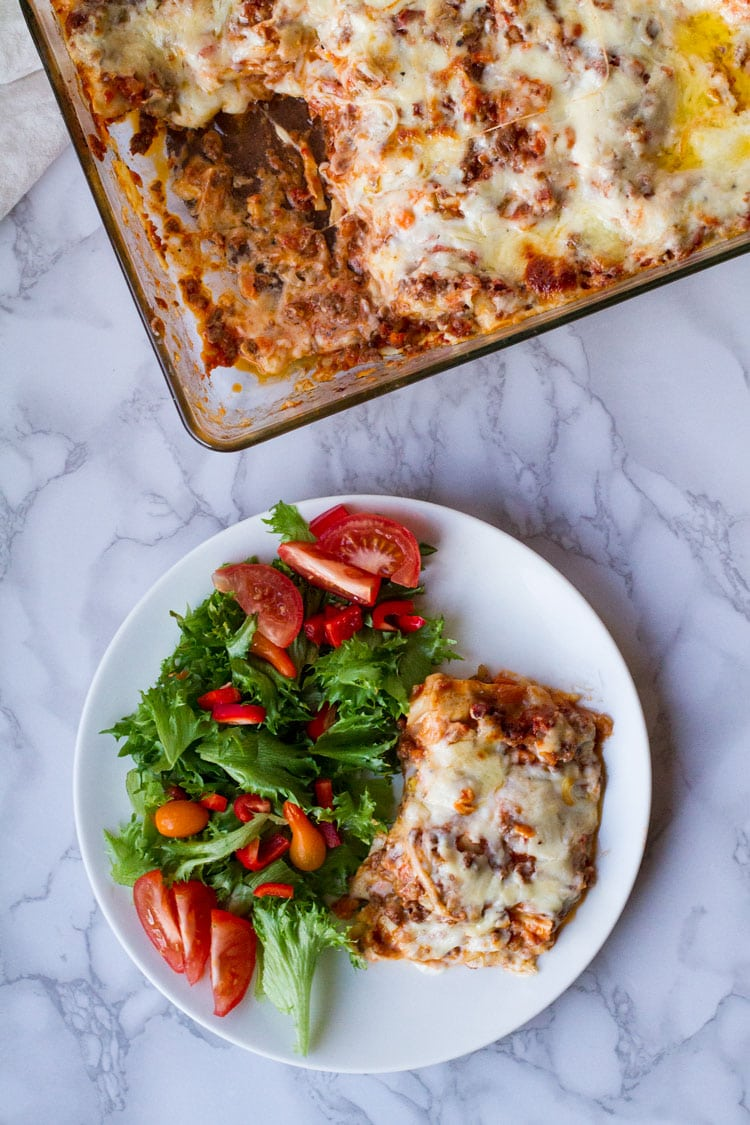 Lasagna and side salad on a white plate, marble table. Flatlay.
