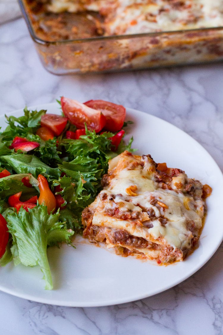 Lasagna and a side salad on a white plate. The whole dish in the background.