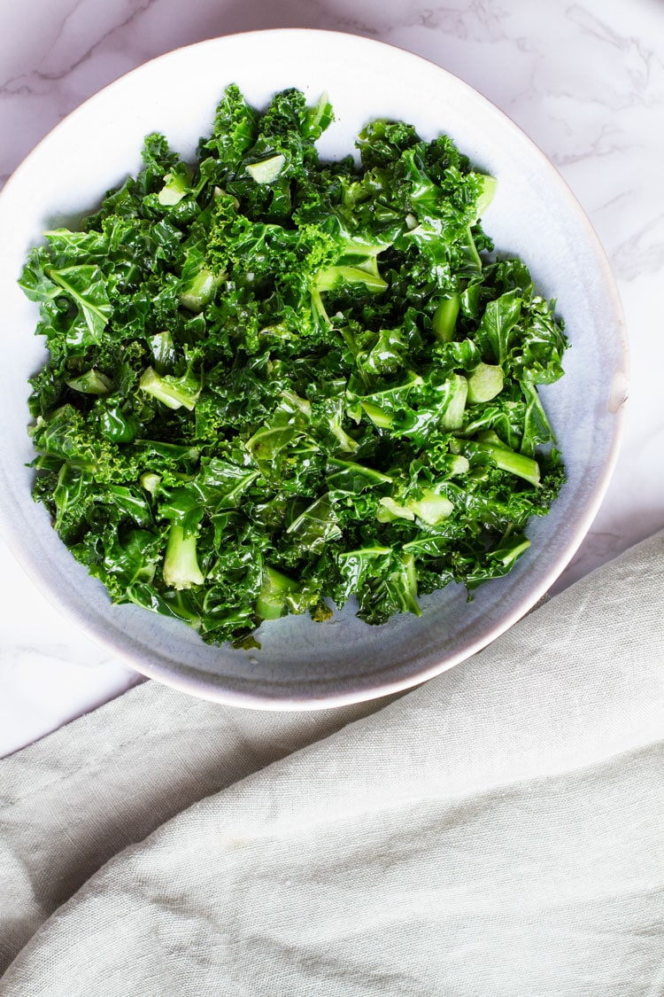 Big bowl of sauteed kale. Pastel green linen on the side.