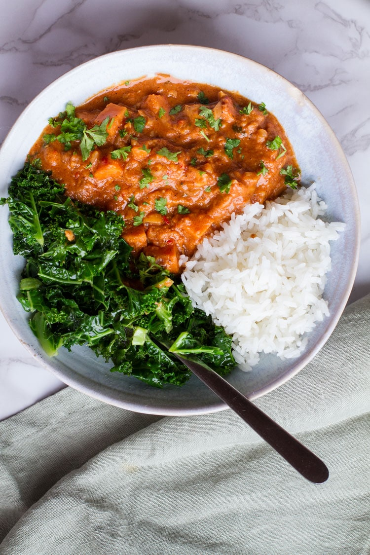 Wilted kale, peanut stew and steamed rice in a big bowl. Flatlay on white marble background.