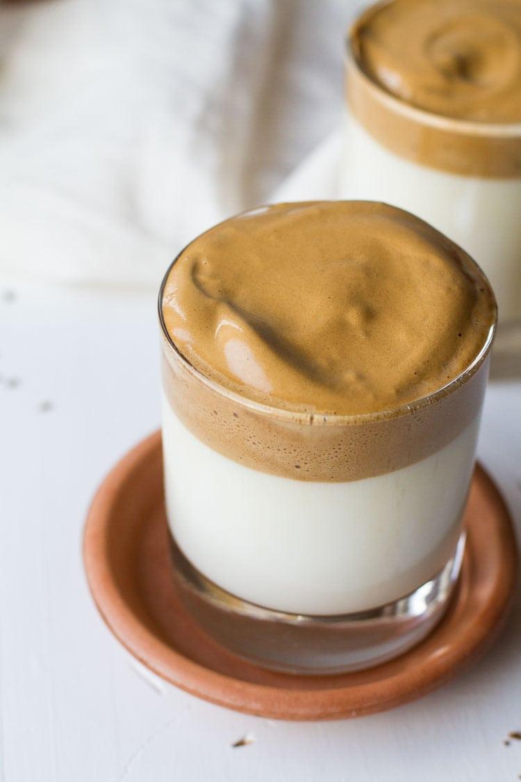 Glass with dalgona coffee and milk.