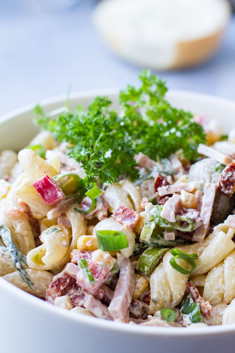 Creamy pasta salad in a white bowl, garnished with parsley.