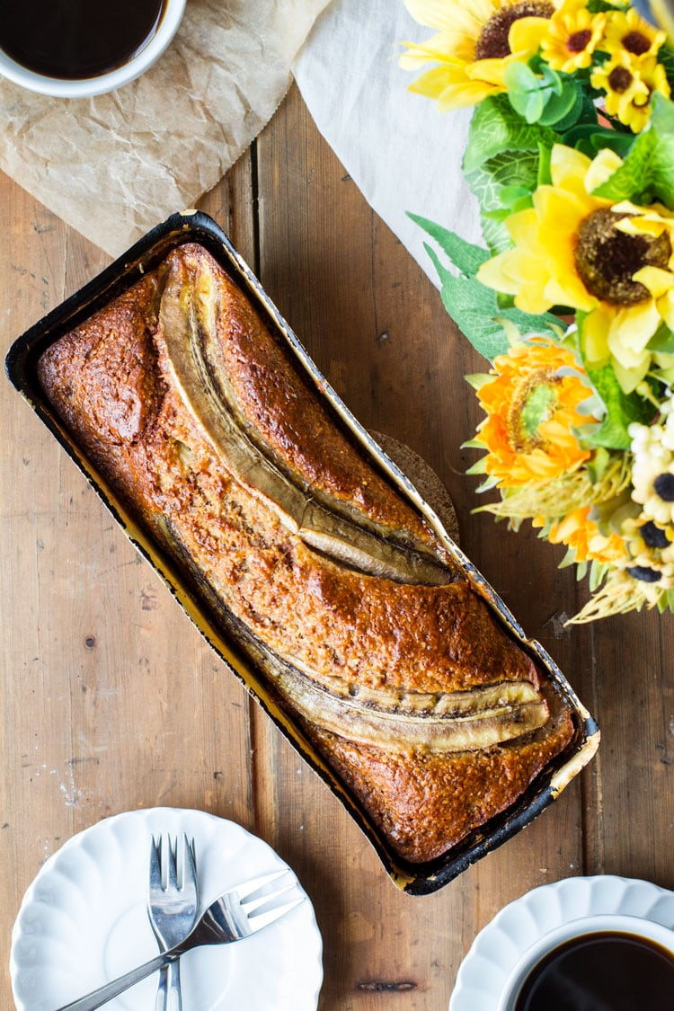 Banana bread with halved bananas on top, still in the load pan.
