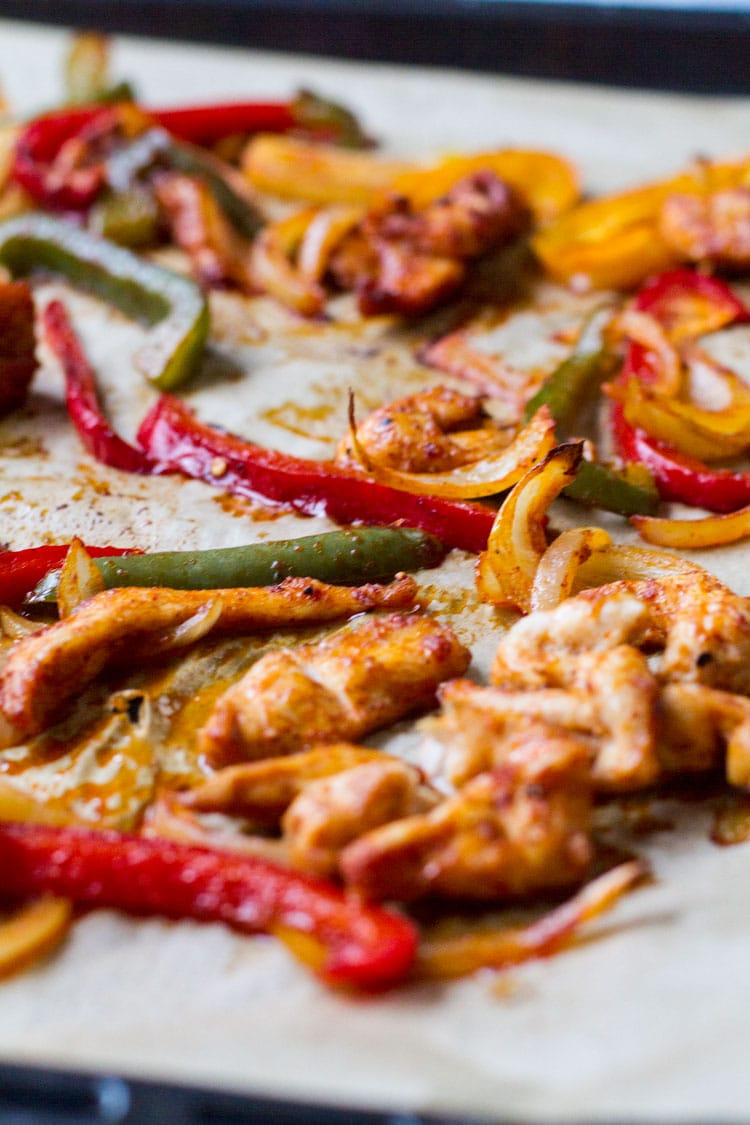 Close-up of cooked chicken fajitas on the baking sheet.