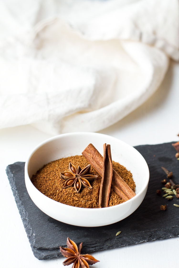 Chinese five spice in a small white bowl, garnished with star anise and cinnamon sticks.