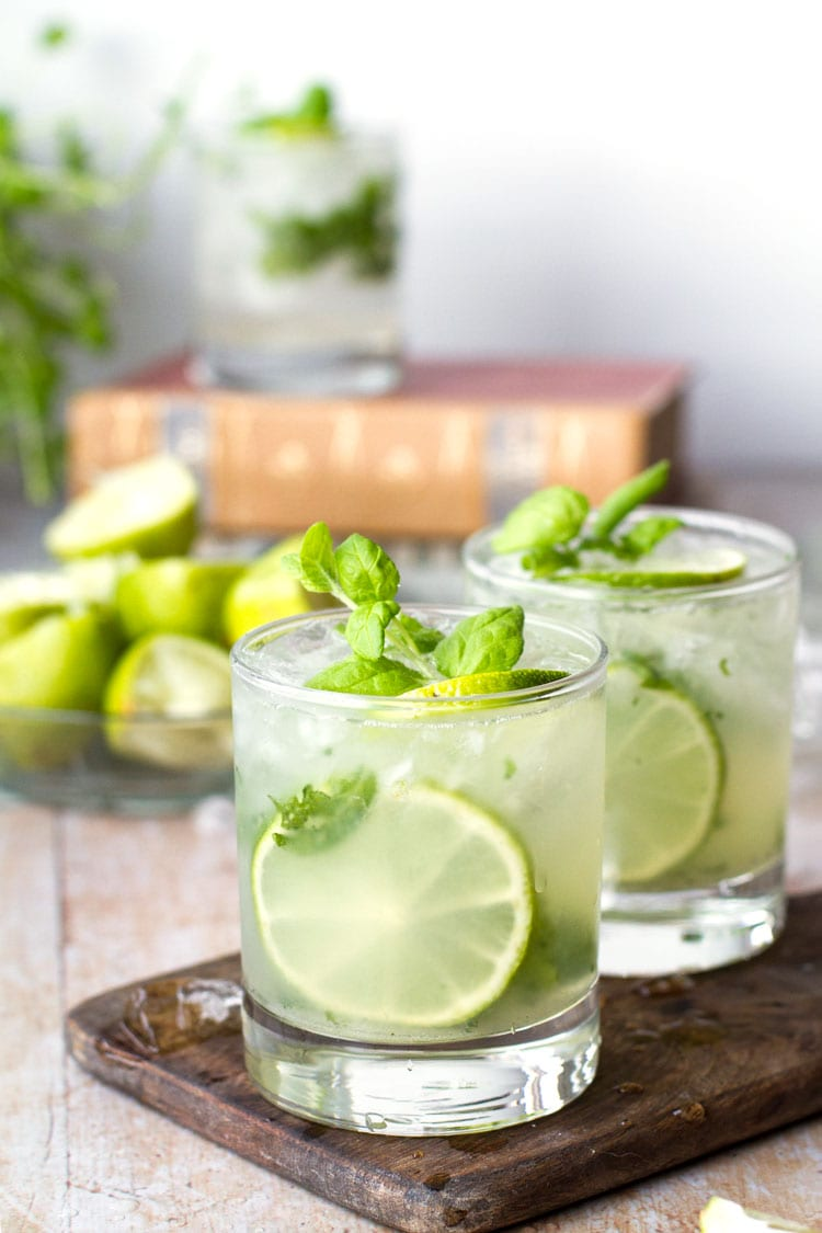 Two glasses on a wooden board, filled with mojito, lime and mint.