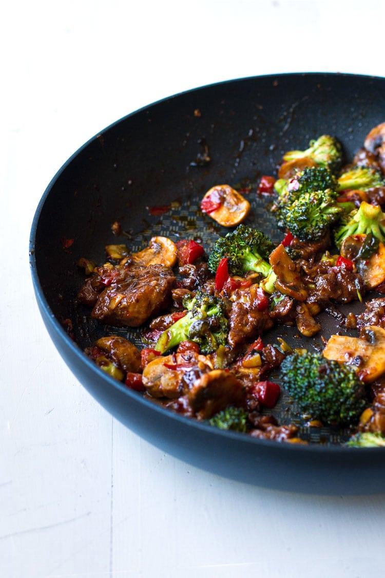 Sautéed vegetables and pork in skillet.