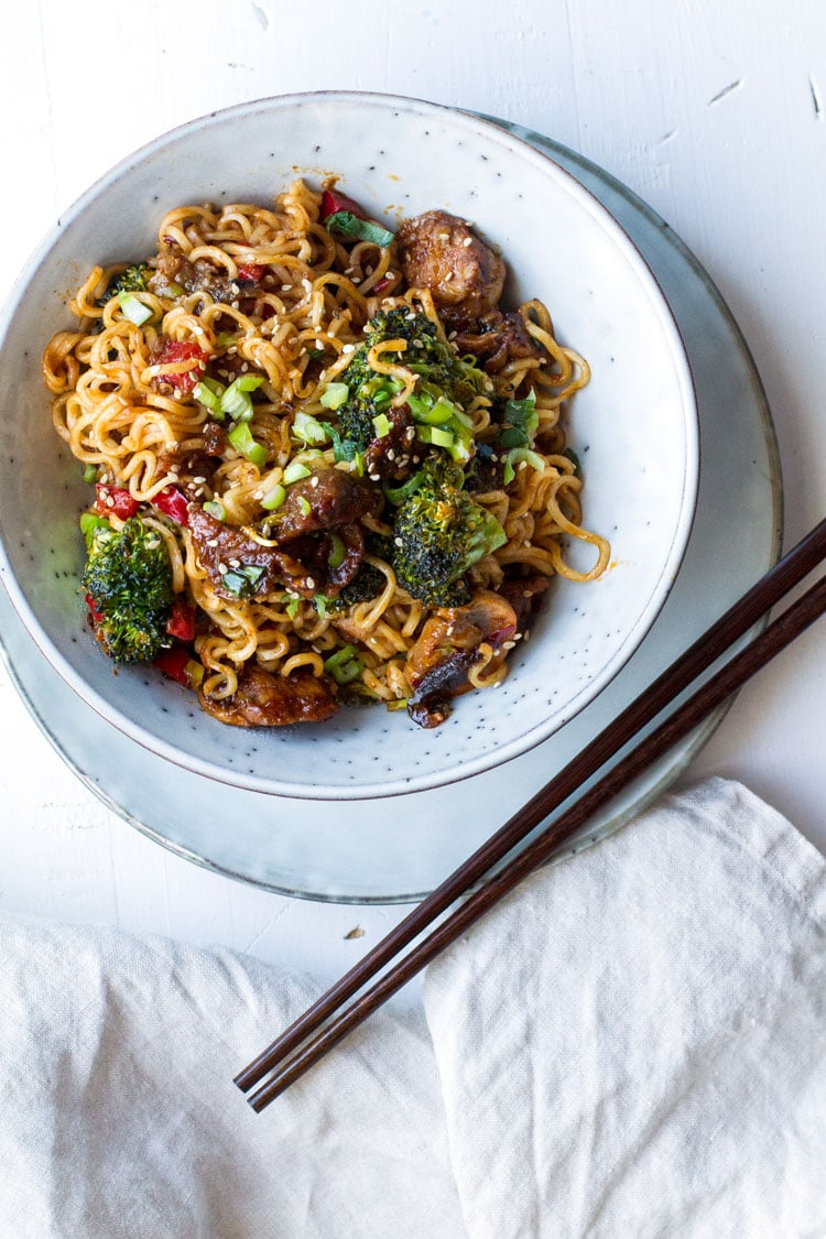 Bowl with pork stir fry and noodles. Chopsticks on the side.