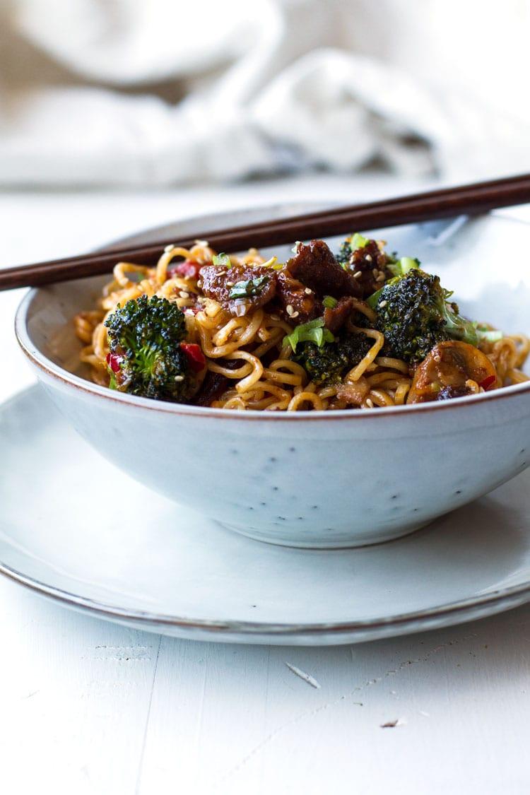 A bowl of pork stir fry with noodles.