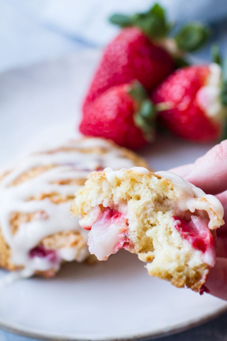 Hand holding a piece of the scone to show the insides.