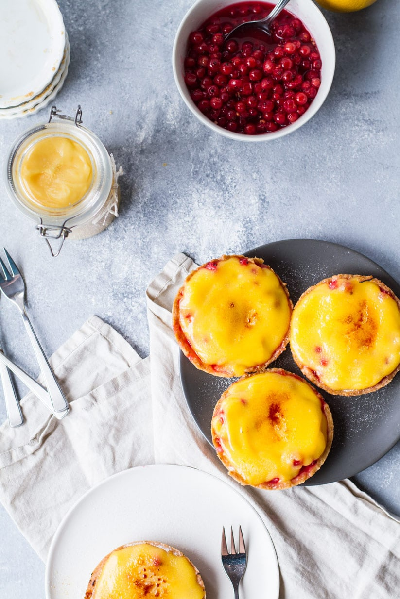 Lemon curd and red currants brulee tarts on a dark plate.